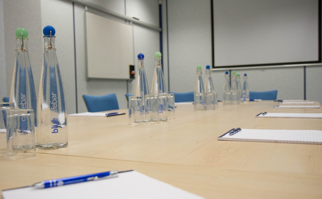 Shot of Garda room with notepads, pens, bottles of water and glasses on boardroom table at The Ark Conference Centre in Basingstoke Hampshire